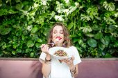 Young And Beautiful Woman Enjoying Heathy Salad Sitting At The Vegetarian Restaurant With Living Wal poster