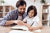 Bearded Father Helps Young Son To Do School Homework . Kid Writes In Copybook. Self Education Concep poster