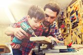 family, carpentry, woodwork and people concept - father and little son with drill perforating wood p poster