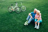 Cheerful Senior Couple Sits On The Grass, Enjoying The Rest After Riding Bicycles. Bicycles Stand Ne poster