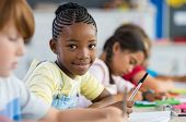 Smiling african girl sitting at desk in class room and looking at camera. Portrait of young black sc poster