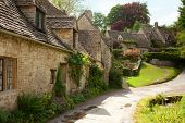 Traditional Cotswold cottages in England, UK.  after the rain. spring. Bibury is a village and civil
