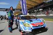 SEPANG - JUNE 10: A team personnel poses with the Toyota Prius car of apr Hasepro Team on the start