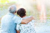 image of old couple  - Senior couple sit embracing and looking at water - JPG