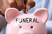 Person Saving Money For Funeral By Inserting Coin In Piggy Bank With Funeral Text poster