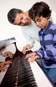 Boy taking piano lessons at home with a tutor
