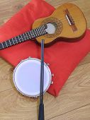 Close-up Of Two Brazilian Musical Instruments: Cavaquinho And Tamborim With Drumstick On A Red Pillo poster