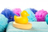 A yellow duck shaped bar of shower soap on a light blue towel with shower poufs against a white background.