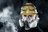 A rescue worker wears a respirator in a smokey, toxic atmosphere.  Image show the importance of prot
