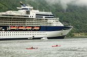 NORDDAL - JUNE 26: Two kayaks, yacht and rescue boat float on fiord near big passenger liner on JUNE 26, 2011 in Norddal, Norway. Norway ranks 19 in world tourism.