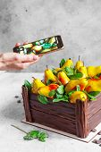 Girl Photographs A Pear Cake With A Smartphone. Birthday Cake In The Form Of A Chocolate Box Filled poster