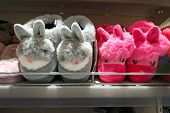 Soft Slippers Bunnies Gray And Pink. Indoor Slippers On Store Shelves. Soft Colored Slippers For Chi poster