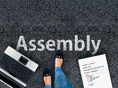Assembly Programming Language. A Woman Steps To A Laptop And Word Assembly On Asphalt. poster