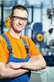 Portrait of young adult experienced industrial worker over industry machinery production line manufa