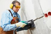 Builder worker making channel for electricity cable with power tool wall chaser