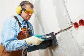 Trabajador constructor que canal de cable de electricidad con rozadora herramienta de poder