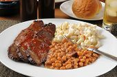foto of brisket  - Closeup of a plate of beef brisket smothered in barbecue sauce - JPG