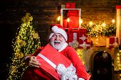 Presents. Christmas. Santa Claus Man Holds Christmas Gift Box. New Year Holidays. Winter. Happiness. poster