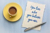 You live who you believe you are - inspirational reminder, handwriting on a white rag paper against  poster