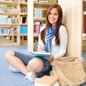Female high school student at library sitting on the floor