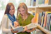 Two female students at school library standing and reading book