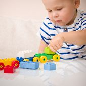 The Boy Plays Colorful Multi-colored Cubes On The Table. Early Development And Learning. Bright Cons poster