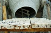 Selective Focus On Group Of Crashed Stones On The Steel Plate With Blurred Concrete Mixer poster