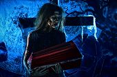 Bloodthirsty witch standing at the night cemetery and holding a coffin.