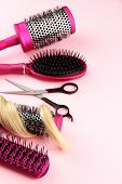 Comb brushes, hair and cutting shears, on pink background
