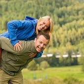 Young smiling couple having fun piggyback riding in the nature