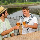 Cheerful male friends drinking beer at sidewalk pub restaurant terrace