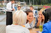 Women gossiping about men sitting at harbor bar summer terrace