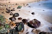 A rocky beach shoreline with blurred water motion in Laguna Beach,California.