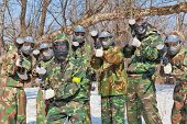 seven friends in masks and camouflage play paintball in the fresh air outdoor