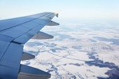 Wing of aircraft and top view of snow-covered small town, road and fields.