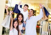 Excited shopping family with arms up holding bags