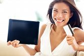 Internet shopping woman online with tablet pc and credit card. Internet shopper buying things on the internet showing blank tablet pc computer as sign. Multicultural Asian Caucasian model happy
