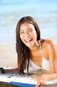 Water sport fun - beach woman bodyboarding surfing on bodyboard or boogieboard. Girl laughing having