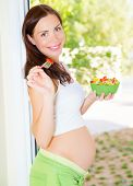 Pretty young lady expecting baby, new life, pregnant female eating tasty sweet fruit salad, happy mo