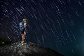 Hiker with backpack standing on top of a mountain with star trails on the background (real stars)