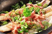 codfish fillets with bacon and spring onion in a pan