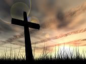 picture of illuminated  - Concept conceptual black cross or religion symbol silhouette in grass over a sunset or sunrise sky with sunlight clouds background - JPG