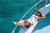 Joyful Brunette Woman Laying On Shipboard Of Yacht. Copyspace