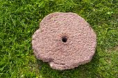 Old Cracked Millstone On Grass