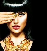 Golden Jewellery. Gold Jewelry. Beauty Brunette Egyptian Style Woman with Gold Accessories and Nails