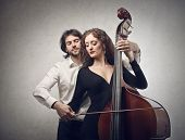 handsome man teaches how to play double-bass to a beautiful woman