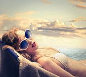 stock photo of sunbathing  - blonde woman in bikini sunbathing on the beach - JPG