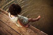 Lone little girl sitting on pier