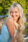 lovely beautiful blonde woman against sunny outdoor greenery