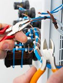stock photo of wire cutter  - Hand of an electrician with tools at an electrical switchgear cabinet - JPG